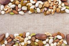 Trockenfrüchte mischen und Vielzahl von Nüssen auf der braunen Sackleinenrückseite Lizenzfreie Stockfotos
