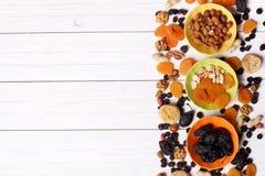 Trockenfrüchte und Nüsse auf weißem hölzernem Hintergrund Lizenzfreie Stockfotos