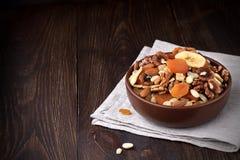 Trockenfrüchte und Nüsse in der Schüssel auf dunklem Holztisch Lizenzfreies Stockbild