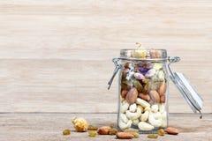 Trockenfrüchte und Vielzahl von Nüssen in ein Flaschenglas auf hölzernem b Lizenzfreie Stockfotos