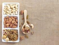 Trockenfrüchte und Vielzahl von Nüssen in einen Teller auf Sackleinen backgr Lizenzfreie Stockfotografie