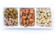 Trockenfrüchte und Vielzahl von Nüssen in einer Schüssel auf dem weißen Tabellenba Stockbilder