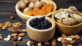 Trockenfrüchtefeigen, -aprikosen, -pflaumen und -nüsse auf hölzernem Hintergrund stock video footage