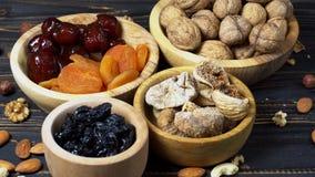 Trockenfrüchtefeigen, -aprikosen, -pflaumen und -nüsse auf hölzernem Hintergrund stock video