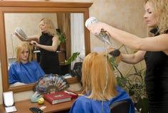 Trocknen des Haares zu Hause vor dem Spiegel Stockfotografie