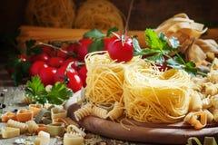 Trocknen Sie italienische Teigwaren Barbine in den Nestern mit Kirschtomaten und -gleichheiten lizenzfreie stockfotos