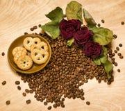 Trocknen Sie rote Rosen und Plätzchen auf Kaffeesamen und hölzernem Hintergrund Stockfotos