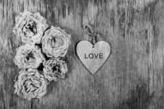 Trocknen Sie verwelkte Rosen und ein Herz auf einem alten hölzernen Hintergrund Stockbild
