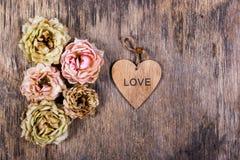 Trocknen Sie verwelkte Rosen und ein Herz auf einem alten hölzernen Hintergrund Kopieren Sie Platz Lizenzfreies Stockfoto