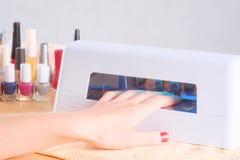 Trocknende Fingernägel unter UVlampe Stockfotos