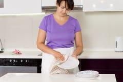 Trocknende große Teller der Hausfrau nach einer Mahlzeit Stockbilder