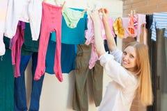 Trocknende Kleidung des positiven langhaarigen Mädchens auf Wäscheleine Stockfotos