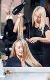 Trocknendes Frauenhaar des Stilisten Lizenzfreies Stockfoto