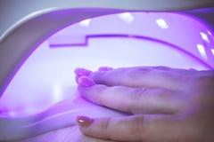 Trocknendes Gel der professionellen ultravioletten Nagelmaniküre-Lampe, das auf Frau ` s Hand in einem Schönheitssalon poliert stockbild