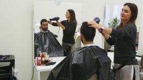 Trocknendes Haar des Berufsfriseurs im Schönheitssalon Männlicher junger Kunde und weiblicher Friseur stock footage
