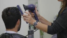 Trocknendes Haar des Berufsfriseurs im Schönheitssalon Männlicher junger Kunde und weiblicher Friseur Abschluss oben stock footage