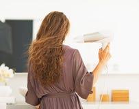 Trocknendes Haar des Frauenschlages im Badezimmer. hintere Ansicht Lizenzfreie Stockfotos