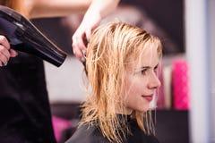 Trocknendes Haar des unerkennbaren Friseurs ihres schönen jungen Cl Stockfotografie