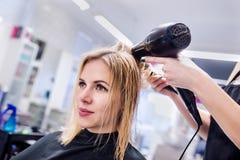 Trocknendes Haar des unerkennbaren Friseurs ihres schönen jungen Cl Lizenzfreies Stockfoto
