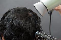 Trocknendes schwarzes Haar nachdem dem Sterben lizenzfreie stockbilder
