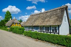 Troense, Denmark - June 26, 2016: Two idyllic half-timbered houses with thatched roof on a sunny day in the town stock images