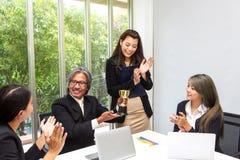 Troféu de vencimento da equipe do negócio no escritório Homem de negócios com os trabalhos de equipe na concessão e no troféu mos fotos de stock royalty free