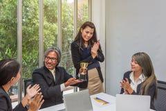 Troféu de vencimento da equipe do negócio no escritório Homem de negócios com os trabalhos de equipe na concessão e no troféu mos fotografia de stock royalty free