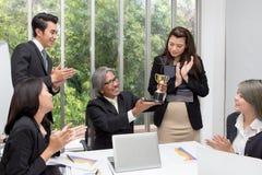 Troféu de vencimento da equipe do negócio no escritório Homem de negócios com te fotografia de stock royalty free