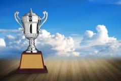 troféus de prata na tabela de madeira com backgroun do céu azul e das nuvens Fotografia de Stock Royalty Free