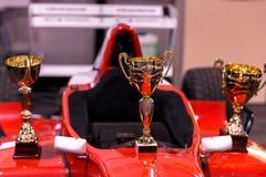 Trofei per il vincitore e la vettura da corsa rossa Fotografie Stock Libere da Diritti
