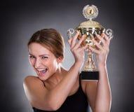 Trofeo de elevación de la mujer joven foto de archivo libre de regalías