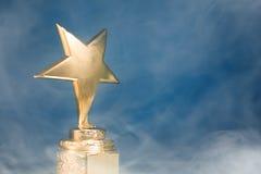 trofeo de la estrella del oro en humo fotos de archivo