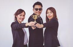 Trofeo de la tenencia del hombre de negocios con los colegas femeninos, foto de archivo