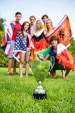 Trofeo del campeonato con los atletas de diversas naciones Imágenes de archivo libres de regalías