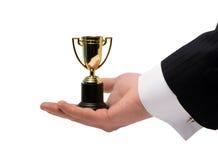 Trofeo del ganador en su mano imagen de archivo libre de regalías