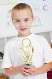 Trofeo della holding del ragazzo Immagini Stock