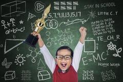 Trofeo feliz del asimiento del muchacho del estudiante en clase Imagen de archivo libre de regalías