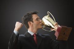 Trofeo que se besa del hombre de negocios Fotos de archivo