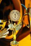 Trofeos para el ganador y la rueda amarilla del coche de competición Foto de archivo