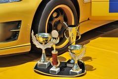 Trofeos y coche de competición amarillo Imagen de archivo libre de regalías