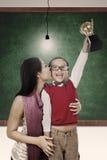 Trofeum i zwycięzca całujemy mum przy klasą Fotografia Stock