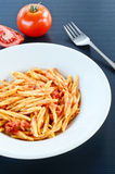 Trofie with ragù. Cooked italian pasta with tomato sauce and meat on black background Stock Photo