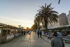 TROGIR, CROÁCIA, O 1º DE OUTUBRO 2017: Passeio dos turistas bens de compra ao comerciante na rua central no por do sol fotos de stock