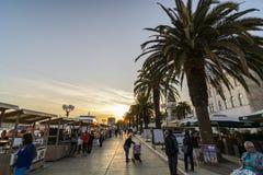 TROGIR, CROÁCIA, O 1º DE OUTUBRO 2017: Passeio dos turistas bens de compra ao comerciante na rua central no por do sol imagens de stock royalty free