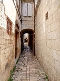 Trogir / Croatia - June 26 2017: Narrow street in the downtown of Trogir. The path of pawing stones royalty free stock images