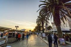 TROGIR KROATIEN, OKTOBER 01 2017: Turister som går gods för en köpande till köpmannen på den centrala gatan på solnedgången arkivfoto
