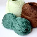 Trois écheveaux pour tricoter brun, vert-foncé et vert clair photo stock