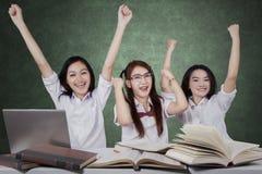 Trois écolières gaies célèbrent le gain Images libres de droits