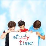 Trois écoliers avec le panneau des textes Images stock