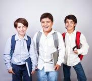 Trois écoliers heureux Photo stock